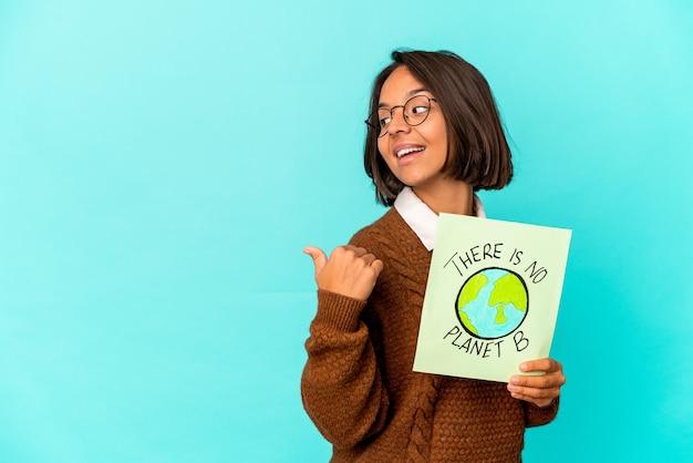 Молодая латиноамериканская женщина смешанной расы, держащая точки плаката спасения планеты с большим пальцем, смеющаяся и беззаботная. Premium Фотографии