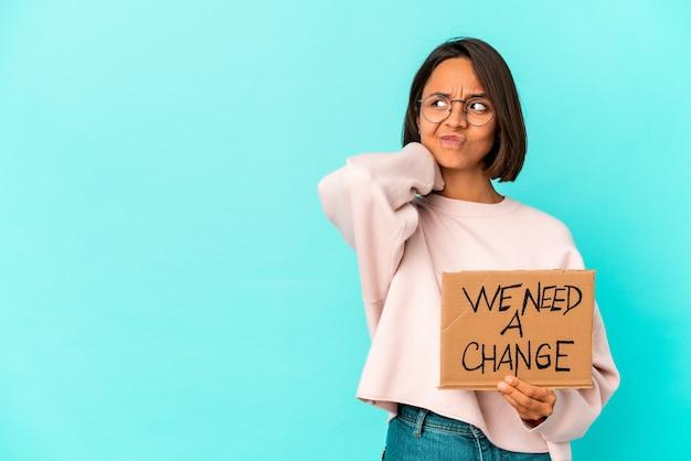 頭の後ろに触れて、考えて、選択をする段ボールに感動的な変更メッセージを保持している若いヒスパニック混血の女性。 Premium写真
