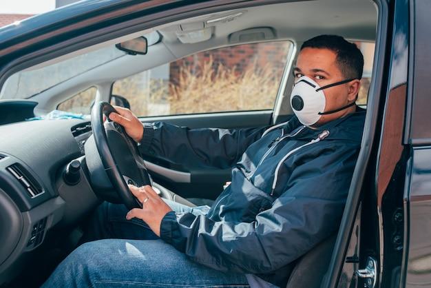 Молодой латиноамериканский таксист в защитной маске и ждет клиента. ковидный 19. коронавирус. Premium Фотографии