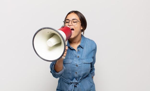 幸せ、興奮、前向きな気持ちで、口の横に手を置いて大きな叫び声を上げ、声をかける若いヒスパニック系女性 Premium写真