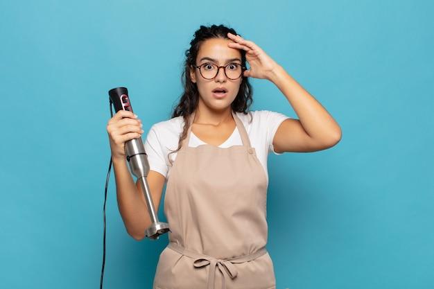 ストレス、心配、不安、または恐怖を感じ、頭に手を置いて、誤ってパニックに陥っている若いヒスパニック系女性 Premium写真