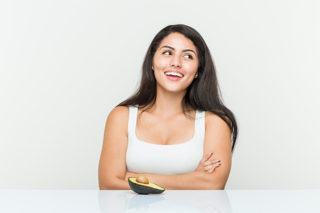 Young hispanic woman holding an avocado smiling confident with crossed arms. Premium Photo