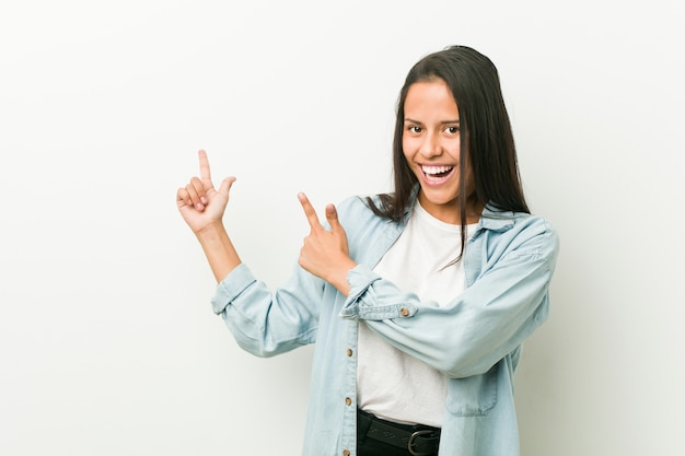 Young hispanic woman pointing with forefingers to a copy space, expressing excitement and desire. Premium Photo