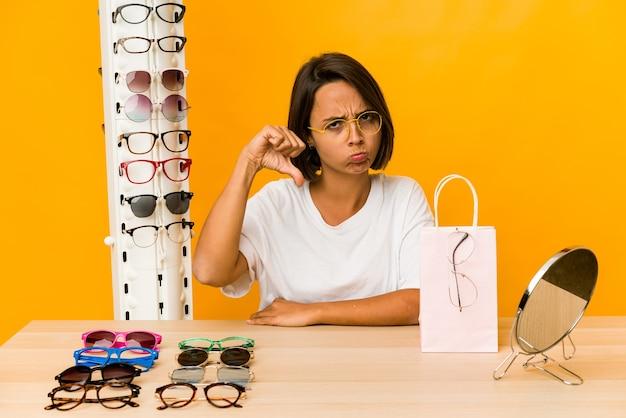 嫌いなジェスチャーを示して、親指を下に向けて孤立した眼鏡をかけようとしている若いヒスパニック系女性。不一致の概念。 Premium写真