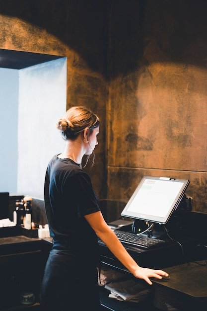 Young hostess standing near cash register Free Photo