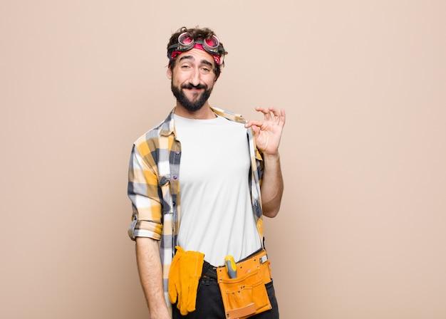 若い家政婦の男は傲慢で成功した、前向きで誇りに思って、平らな壁に自己を指して Premium写真