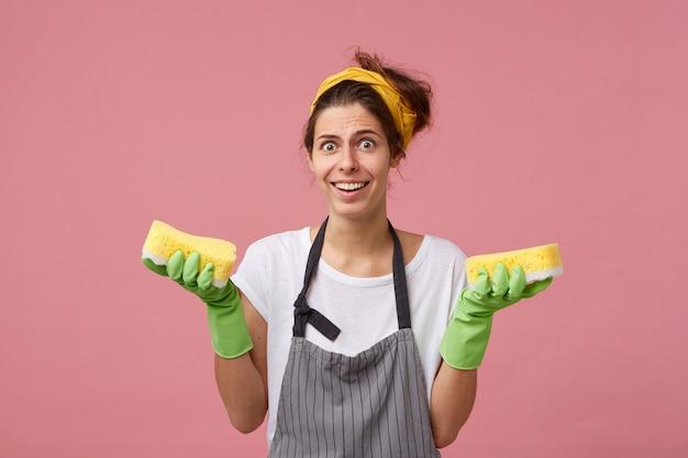 Молодая горничная в фартуке и резиновых перчатках держит в руках две чистые губки, глядя с удивленным выражением лица, широко улыбаясь, показывая свои белые идеальные зубы. весенняя уборка Бесплатные Фотографии