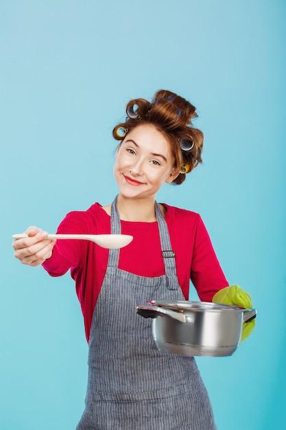 Молодая домохозяйка дает вам половник попробовать домашний суп Бесплатные Фотографии