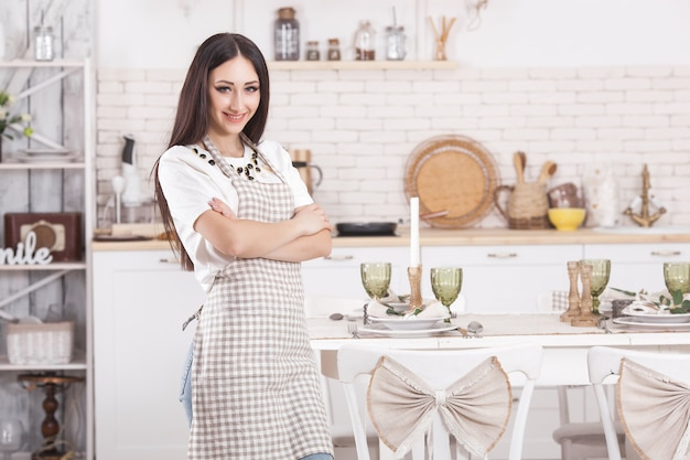 Young housewife on kitchen background. woman at home kitchen. female cooking with copy space. Premium Photo