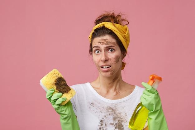Giovane casalinga che osserva sorprendentemente con espressione insoddisfatta Foto Gratuite