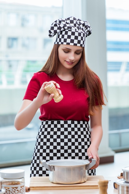Young housewife preparing soup in kitchen Premium Photo