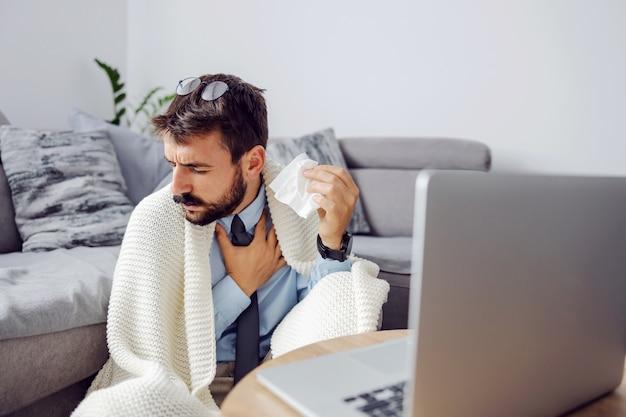 Молодой больной бизнесмен, держащий носовой платок и кашляющий, сидя дома и используя ноутбук. Premium Фотографии