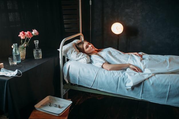 病院のベッドで横になっている若い病気の女性 Premium写真