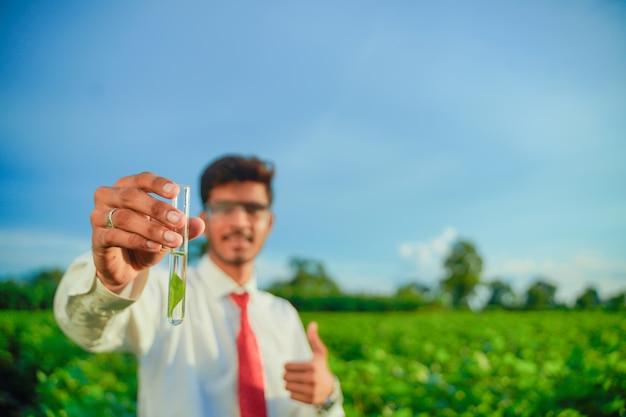 試験管、農業および科学者の概念を持つ若いインドの農学者。 Premium写真