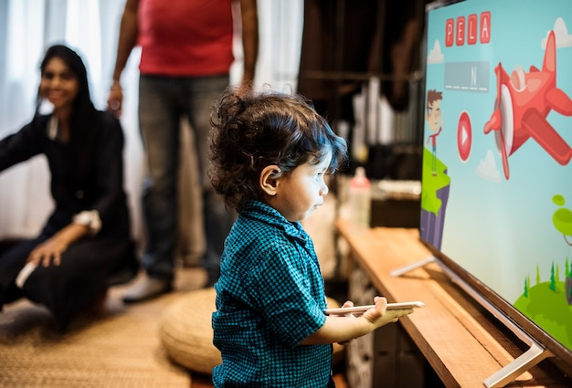 Young Indian boy watching television Free Photo