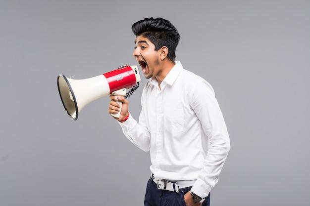 Giovane uomo d'affari indiano che annuncia in un megafono sulla parete grigia Foto Gratuite