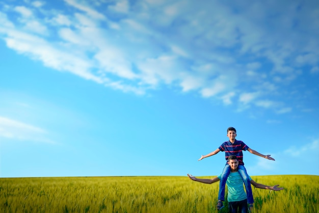 Young indian child with blank poster at indian wheat field Premium Photo