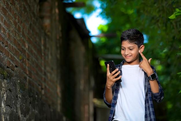 Молодой индийский милый ребенок со смартфоном Premium Фотографии