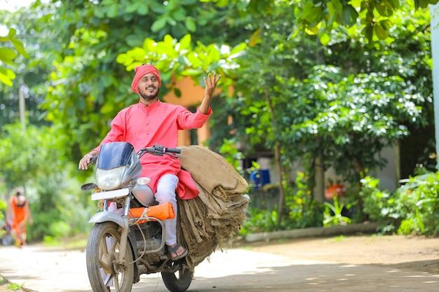 若いインドの農民はバイクで荒布袋を収集します Premium写真