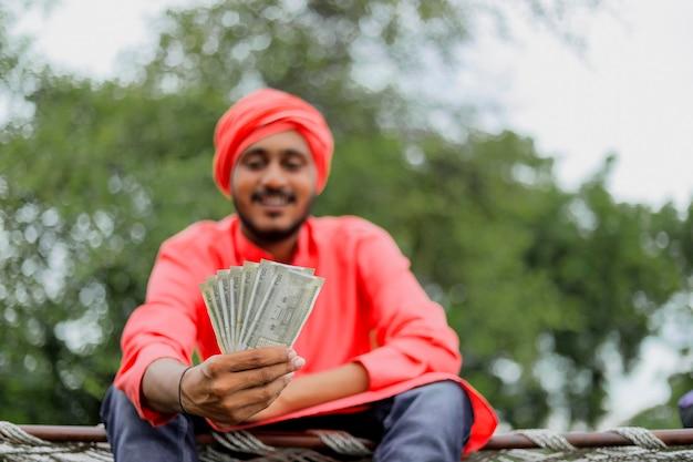お金を数えて見せている若いインドの農夫 Premium写真