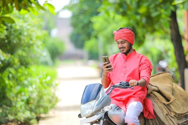 バイクとスマートフォンを使用して若いインドの農民 Premium写真
