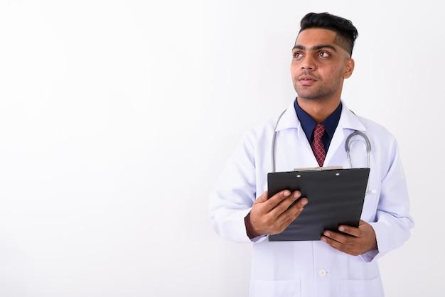 Молодой индийский мужчина врач на белом Premium Фотографии
