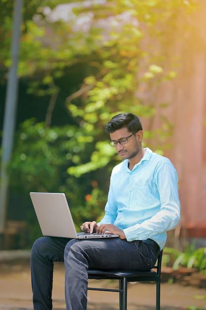 Young indian man using laptop , working on laptop Premium Photo