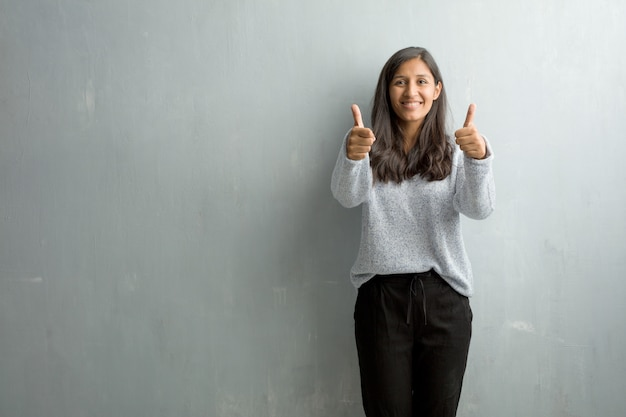 Young indian woman against a grunge wall cheerful and excited, smiling and raising her thu Premium Photo