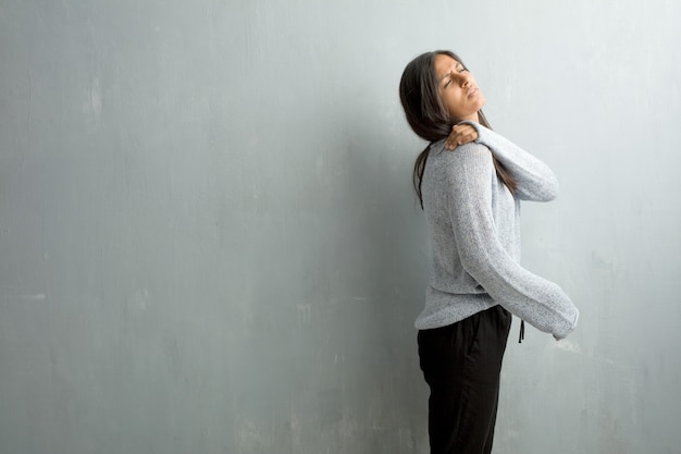Young indian woman against a grunge wall with back pain due to work stress Premium Photo