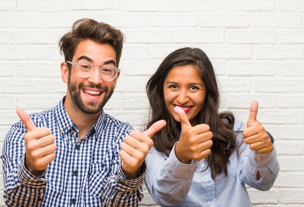 Young indian woman and caucasian man couple cheerful and excited, smiling and raising her thumb up, concept of success and approval, ok gesture Premium Photo