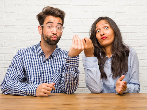 Young indian woman and caucasian man couple doing a typical italian gesture Premium Photo