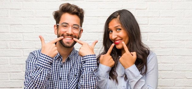 Young indian woman and caucasian man couple smiles, pointing mouth, concept of perfect teeth, white teeth, has a cheerful and jovial attitude Premium Photo