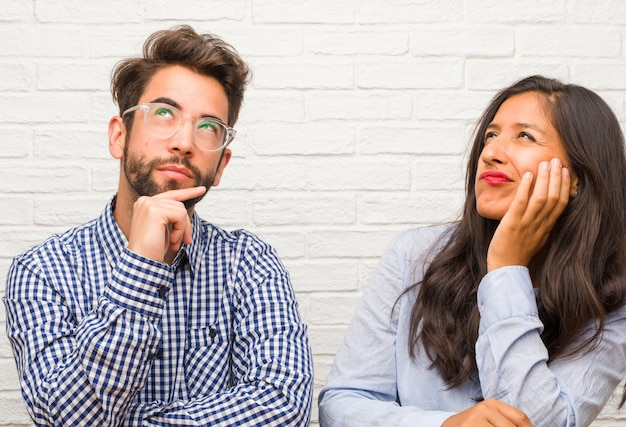 Young indian woman and caucasian man couple thinking and looking up, confused about an ide Premium Photo