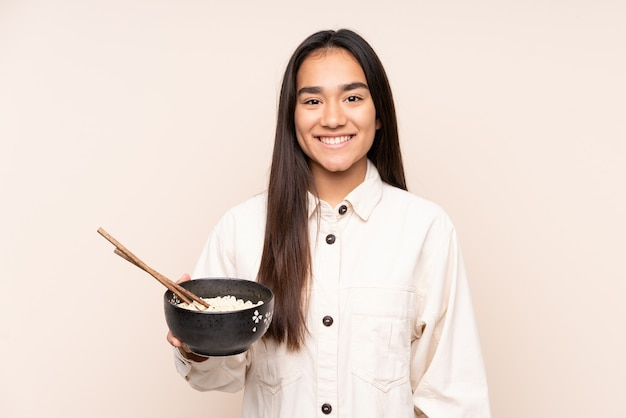 Молодая индийская женщина изолирована на бежевом, много улыбаясь, держа миску лапши с палочками для еды Premium Фотографии
