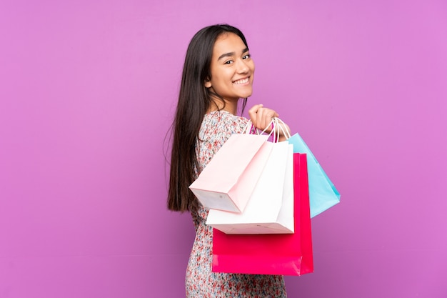 ショッピングバッグを保持し、笑顔の紫色で孤立 Premium写真