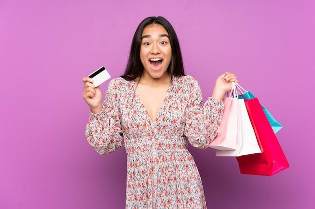 紫色の買い物袋を持って孤立し、驚いた若いインド人女性 Premium写真