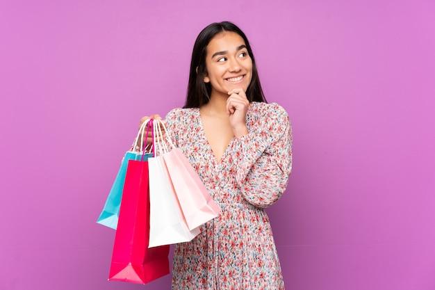 ショッピングバッグを持って考えている紫色に孤立した若いインド人女性 Premium写真