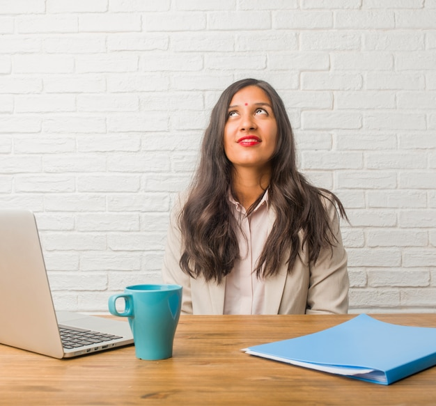 Young indian woman at the office looking up, thinking of something fun and having an idea, concept of imagination, happy and excited Premium Photo