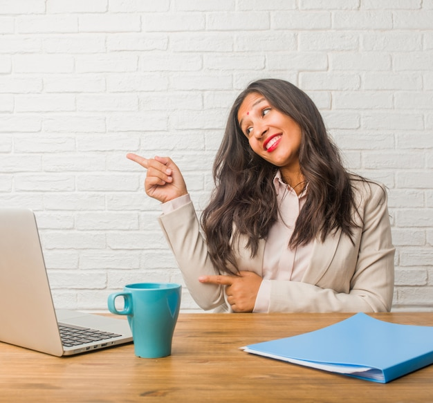 Young indian woman at the office pointing to the side, smiling surprised presenting someth Premium Photo