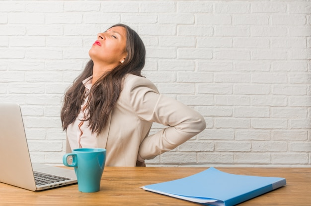 Young indian woman at the office with back pain due to work stress, tired and astute Premium Photo