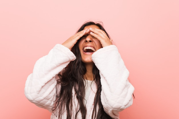 Young indian woman wearing pajama covers eyes with hands, smiles broadly waiting for a surprise. Premium Photo