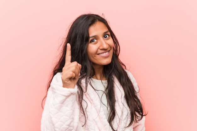 Young indian woman wearing pajama having an idea, inspiration concept. Premium Photo