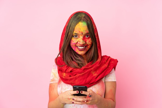 Young indian woman with colorful holi powders on her face on pink wall sending a message with the mobile Premium Photo