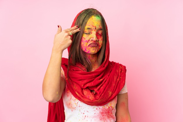 Young indian woman with colorful holi powders on her face on pink wall with problems making suicide gesture Premium Photo