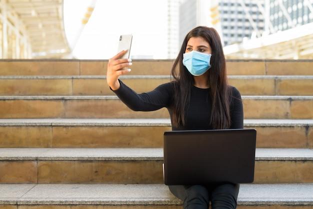 Молодая индийская женщина с маской, используя ноутбук и видеозвонок с телефоном у лестницы в городе Premium Фотографии