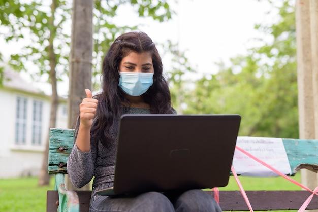 Молодая индийская женщина в маске делает видеозвонок и показывает палец вверх, сидя на скамейке в парке Premium Фотографии