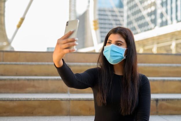 Молодая индийская женщина с маской, видеозвонок с телефоном и сидящая у лестницы в городе Premium Фотографии