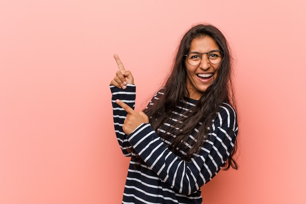 Young intellectual indian woman pointing with forefingers to a copy space, expressing excitement and desire. Premium Photo