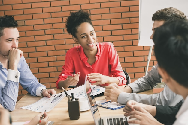 Young interracial business people paying attention to their  friend in group discussion Premium Photo