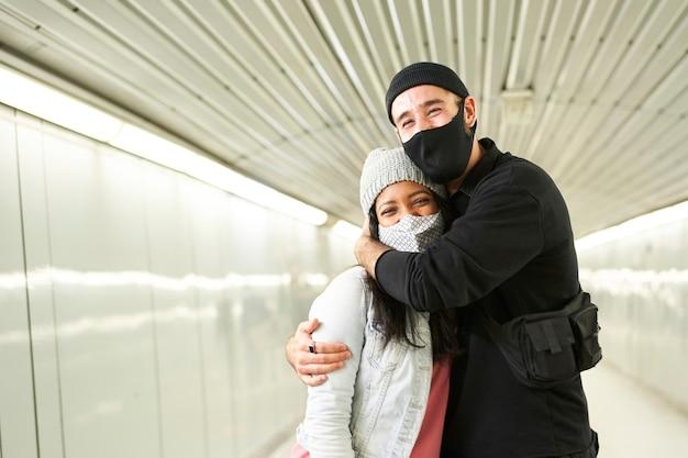 Молодые межрасовые пары обнимаются в коридоре подземного метро. Premium Фотографии